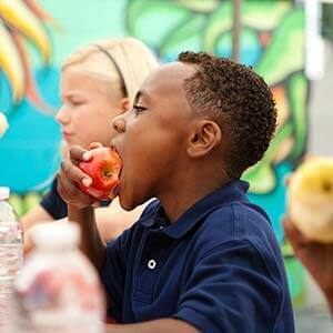 Image of a child eating an apple at school